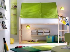 Ein kleines Kinderzimmer mit umbaufähigem KURA Bett in Weiß/Kiefer und KURA Baldachin in Grün/Weiß mit viel Platz zum Schlafen und Spielen