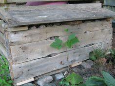 Hyönteishotelli trukkilavasta. Täynnä kiviä. Iso ja ruma, mutta huomaamaton kompostin kyljessä.