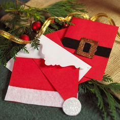 Santa-Inspired Christmas Cards --   Make Christmas cards inspired by Santa's suit using red and white construction paper, black ribbon, and glitter. #tutorial