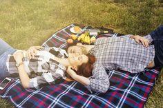 Sonriendo cariñosa pareja joven tendido en una manta sobre la hierba verde Foto gratis