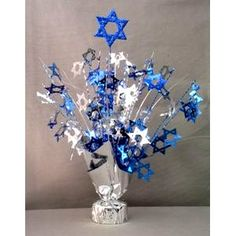 for a bigger centerpiece; tie ribbon to helium filled blue and silver balloons and secure inside or around the base....if more weight is needed set this spray inside a large vase or ? and fill with colored centerpiece marbles; rocks; sand or whatever.....Glitter Top Star of David Weight