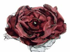 A personal favorite from my Etsy shop https://www.etsy.com/listing/98312064/wedding-hair-flower-red-wine-satin