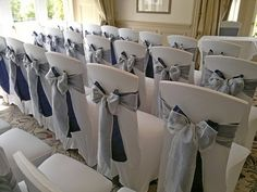 White chair covers with navy and silver bow sashes