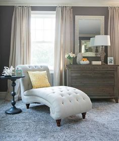 Elegant bedroom features a linen tufted French chaise lounge next ...
