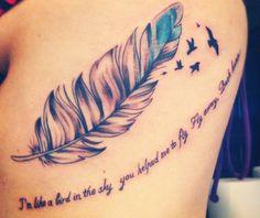 chica con un tatuaje en forma de pluma de ave con una frase sobre su espalda