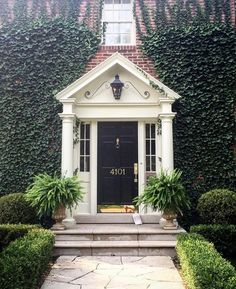 Climbing ivy and boxwoods frames traditional black and white entry.