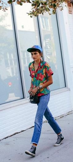 Langley Fox in a printed shirt, ball cap, jeans and Converse sneakers