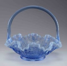 An antique Fenton glass fruit basket, in periwinkle blue, with ripple edges and floral detail to sides.