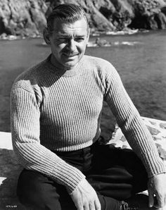"""""""Between Scenes Clark Gable in sweater and slacks he wears for his part as Philip Sutherland in M-G-M's dramatic love story """"Never Let Me Go"""" in which he stars with Gene Tierney. Much of the film was shot on location at Mullion Cove, Mevagissy and..."""