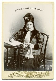Studio portrait of Dvora Esther Gelfer (1817-1907) philanthropist and founder of a gmiles khesed, with an elaborate bonnet and shaytl. Vilna, before 1907.
