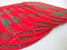 Featuring a gold thread woven through the red and green plaid, these vintage placemats are a festive addition to any holiday meal! Plaid fabric is an open weave, back appears to be a cotton/poly blend, in which they are also bound. There is also a middle layer, probably polyester batting. They measure 12.5 x 18 5/8 inches (31.8 x 47.3 cm).  Excellent condition! These are from my mother-in-laws estate. She love to entertain, and these were always on the table during the Christmas season…