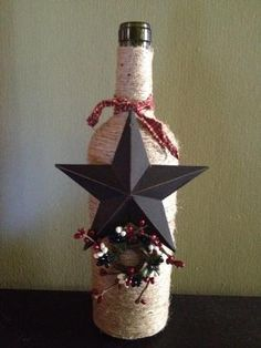 Wine bottle wrapped in jute twine with a metal star and some small decorations. Sure to add a beautiful touch to your home. by Judy Scroggins Evans