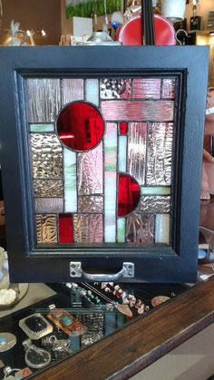 Beautiful stained glass original abstract design. This panel is in a striking black frame with window latch details. features red, green and clear stained glass measures 13 1/4 by 11 1/4. depth is 1 1/2 without the window handle. with the window handle the depth is 3.