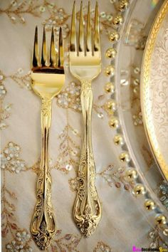 Ideal place setting: -Gold flatware -Clear gold rimmed charger plate with art deco plate on top  -Ivory linens with art deco champagne overlays -Gold rimmed glasses