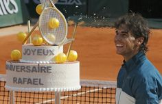 Nadal of Spain looks at with his birthday cake after winning his mens singles match against Nishikori of Japan at the French Open tennis tournament in Paris