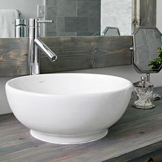 Bowled Over  An unpretentious white vessel sink rests on the simple pine countertop. A gleaming contemporary faucet offers the stylized look of an old hand pump, which reminds the homeowner of a vintage wash basin and pitcher.