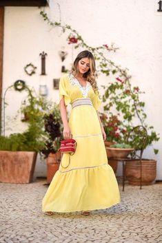 Look da Thássia Naves com vestido amarelo longo e detalhes em rendas, combinando com uma bolsa vermelha – perfeito para tardes quentes de final de semana