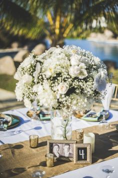 Beach Wedding Flower centerpieces: White roses, Baby's Breath, Orchids and hydrangeas. Burlap runner, gold mercury votives (bought at target, crate and barrel, marshals) Vintage gold frames (Bought at Homegoods and Marshals) Center piece personalized with grandparents civil wedding picture. Table numbers made with chalkboard paper and chalk (Michael's)