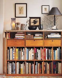 The armoire's inspiration was this bookcase above, which Joelle found, abandoned, in a former apartment. She thinks it was originally a music center; now it displays her absolute favorite books and an assemblage of objects in black, brown, and white, including a tag-sale handblown glass hurricane lamp, prints picked up at junk and antiques shops, brown Wedgwood pitchers, and a lacy frond of seaweed.
