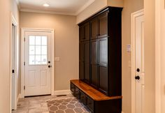 Black lockers in mud room / garage entry with gray tiles and walls - Farinelli Construction