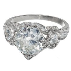"""Antique Art Deco 2.59ct Transitional Cut Platinum Diamond Ring 1930 Stunning 1930-1940 Art Deco original solid Platinum ring with one of the most brilliant sparkly diamonds we have seen in a while. Transitional Ideal cut and blue florescence give the diamond a spread of over 3.00ct diameter and face up mostly white color with just a hint of warm color. The setting is fantastic with side diamonds, hand engraving, open work and """"V"""" shaped Art Deco prongs."""