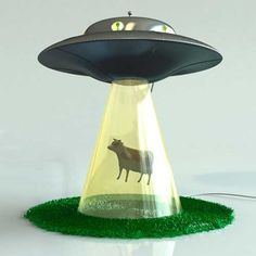 """Alien Abduction Lamp by Lasse Klein: The light in the UFO illuminates the windows with its """"aliens"""" and also the glass beam."""