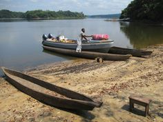 A staff member unloads supplies at the Tsam Tsam Ecotourism Site on Lake Oguemoué, Gabon, Central Africa. Africa, Boat, Dinghy, Boats, Afro