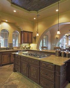 Diese toskanische Küche mit Bögen Design hat Panel Schränke, dunklen Holz Schränke und grauen Backsplash erhoben. Es gibt eine Kochinsel mit Granit-Arbeitsplatten und braunen Holz Schränke voller. Es gibt auch Mitte große Rundbogenfenster und Schrank unter der Spüle. Es hat auch eine Küchenbar mit Granit-Arbeitsplatten auch. Die Beleuchtung ist einfach aber biegen mit dem übergreifenden Thema der Farbe der Küche. Foto von Vanguard Studio Inc.   Blick für mediterrane Küche Design Inspiration