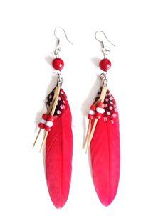 Prachtige opvallende oorbellen met echte veren hangend onder een opvallende kraal in dezelfde kleurstelling. Op de lange veer een klein gestippeld veertje en subtiel suede vetertje met kraaltjes. Lengte ca. 11,5 cm. Kleur rood. Zie afbeelding.