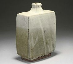 SHOJI HAMADA; BOTTLE VASE | Press-moulded, stoneware, the top section with mottled grey (tiny nick to the foot ring) 8 3/4 in (22.3 cm) high