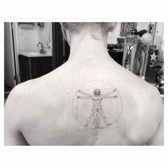 Single needle Vitruvian Man tattoo on the upper back.