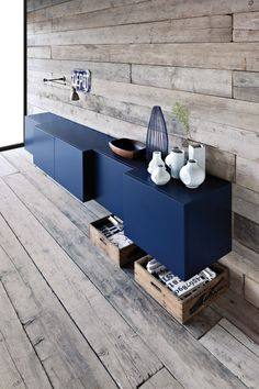 Floating modern navy cabinet and grey rustic wood ship lap walls.