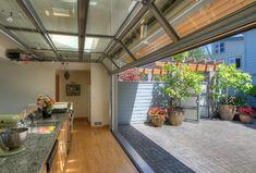 Courtyard kitchen with door up. beach style kitchen