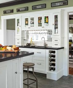 A frequent entertainer added this wet bar to his kitchen addition. Structural posts determined the length of the bar, which he fitted with small drawers for corkscrews and other cocktail accoutrements; a double-drawer fridge for mixers under the counter on the left; and, for symmetry, a look-alike panel on the right that tilts out to access plumbing for the sink. In the upper cabinets, puck lights illuminate liquor bottles. | Photo: Lisa Romerein
