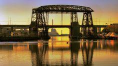 Transbordador Nicolás Avellaneda. Único en América (ocho en el mundo). Construido en Inglaterra en hierro y cobre, armado en Buenos Aires en 1914. Posee un puente superior horizontal de 77,5 m de luz, y una altura libre de 43,2 m sobre el cero del Riachuelo. Dos grandes pilares sirven de apoyo anclados a la cota -24 m. La plataforma suspendida de 8 x 12 m, tirada por cables, se operaba desde el transbordador o de una sala de máquinas. Operó hasta 1960. A su lado el puente vial inaugurado en… Freestyle Rap, George Washington Bridge, Southern Comfort, Most Beautiful Cities, Sydney Harbour Bridge, Marina Bay Sands, Geography, South America, Madrid