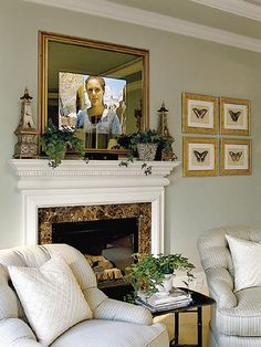 Above the fireplace is an oversize mirror that disguises a TV. When the set is turned on, the TV screen can be seen clearly through the transparent mirror surface.