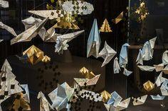 Dans la continuité des vitrines d'Automne de la boutique Relais & Châteaux, Soline d'Aboville met en scène la magie de Noël dans un tourbillon d'origamis. L'or scintille et se mêle aux cartes géographiques, conférant à l'installation un aspect festif. Photos © Géraldine Bruneel