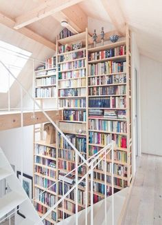 22 bookshelf decorating ideas, including this fantastic floor-to-second-level-ceiling bookshelf wall, complete with catwalk!