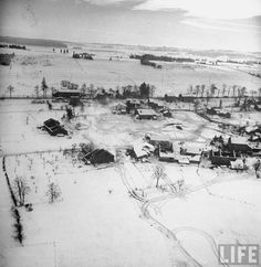 Aerial view over Ardennes showing village battered from Battle of the Bulge fighting.