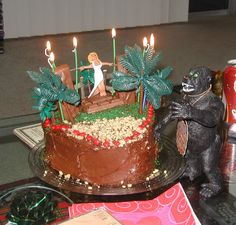 King Kong cake! heart shaped chocolate cake with hand sculpted & painted Fay Wray tied to two snickers bars on steps of kit kats with green sugar grass and walnut sand. The candles sparkle when lit. King Kong was found on ebay.