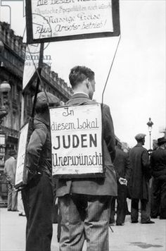 """Man carrying a sandwich board sign for a restaurant in Paris with an anti-semitic advertisement, 1940 (b/w photo). Sign reads: """"German dishes, good prices, and Aryan ownership"""" - and forbids Jews from the restaurant premises"""