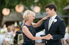 Mother son wedding dance at an outdoor wedding with lanterns in the background.