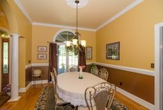 Traditional Dining Room with Columns, Chair rail, Hardwood floors, Crown molding, Carpet, Chandelier