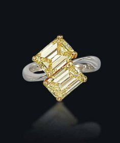 A TWIN-STONE COLOURED DIAMOND RING, BY GRAFF   Set with two fancy intense yellow rectangular-cut diamonds, each weighing approximately 2.04 carats, to the gold hoop, ring size 5¼, in black leather Graff case  Signed Graff, no. 9545