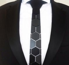 Unique and eclectic, HEX TIE Honeycomb tie is made of lightweight matte black polymers embodying the shape of recurring hexagons. Assembled by hand, each tie reflects a custom setting, giving each pie