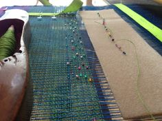 Weaving small glass beads into the linen textile.
