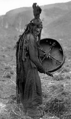 "This shaman wears an upright plume of feathers for a headress. ""Snakes"" hang down the back. Note that the drum is constructed with cross pieces and has what appears to be bells or jingle cones hanging inside the drum."