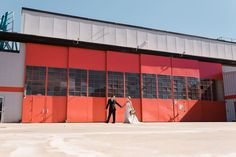 bride and groom in front of our Hangar doors! www.stanleymarketplace.com/hangar/ venue The Hangar at Stanley/ floral + design Cheri Taunton, Southern Charm Wedding and Events/ event planner + design Danielle Odil, Entwined Events/ hair + makeup Rachael Peffer, Glam Team Colorado/ cake Sugar Plum Cake Shoppe/ rentals Colorado Party Rentals/ invitations + paper goods Tasha Rae Designs/ groom's suit Armani/ bridal gown The Bridal Collection/