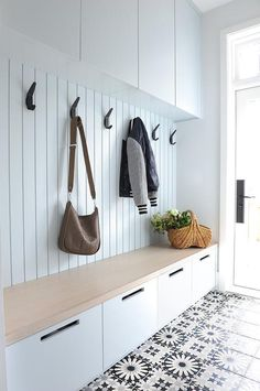 Adding black iron hooks on a white mudroom plank wall creates a stylish and functional addition to a gray wash and wood top bench.