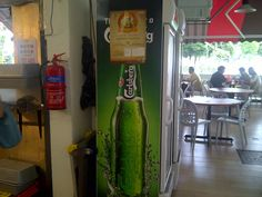 Side of fridge, in front of drinks stall